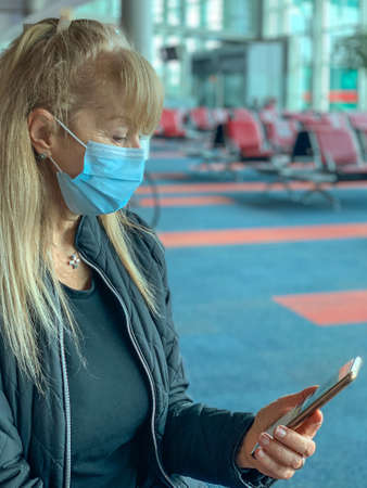 Adult woman looking at her mobile phone in the airport terminal wearing a surgical mask during the covid pandemic 版權商用圖片