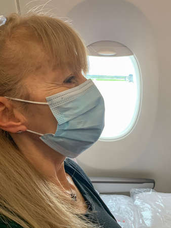 Adult woman on the plane wearing a surgical mask during the covid pandemic