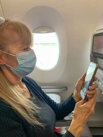 Adult woman looking at her mobile phone on the plane Wearing a surgical mask during the covid pandemic 版權商用圖片
