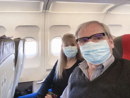 Adult couple taking a selfie while traveling by plane wearing a surgical mask during the covid pandemic.