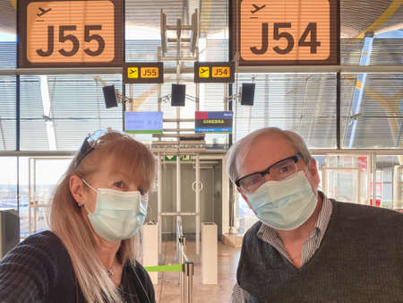 Mature couple taking a selfie in front of the gate for the flight.