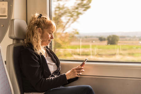 Adult woman traveling alone on the train looking at a mobile. Concept of new naturally
