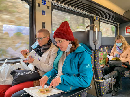 Lausanne, Switzerland - October 11, 2020: Couple on a train with a surgical mask off their face eating from a food tray 新聞圖片