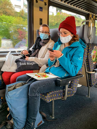 Lausanne, Switzerland - October 11, 2020: Couple on a train with a surgical mask with a food tray facing the smartphone 新聞圖片