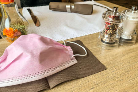 Pink surgical mask on the napkin in a restaurant. 版權商用圖片