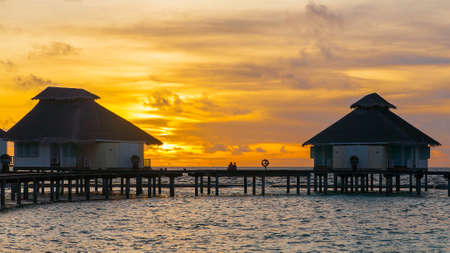 Sunset on tropical island, water villas resort