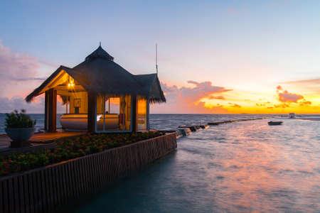 Sunset on tropical Maldives island, water villas resort. Waterhuts at sunset