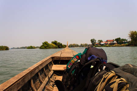 Wooden boat traveling Mekong River. Example of Transportation on Mekong River with backpack - Laos