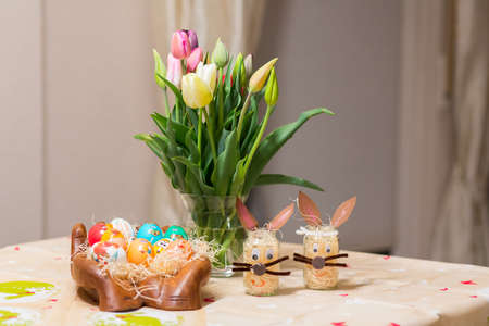 Easter holiday with colored eggs and flowers. colorful tulips near the painted Easter eggs of different colors. Reklamní fotografie