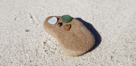 Sandstone, glass and a ladybug on the beach in Helgoland