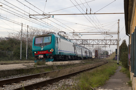 regional: PISA-ITALY: JANUARY, 28 2016: Trenitalia Electric Locomotive E464 is Arriving at a Station with a Regional Passenger Train.