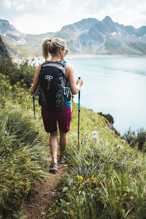 Adventurous Sportive Girl hiking in Beautiful Alpine Mountains next to a Lake