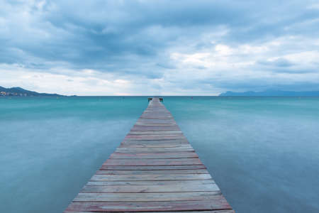 Dramatic Looking Morning at the Sea in Spain - Majorca. Blue Hour with Clouds on the Wooden Pier  Jetty