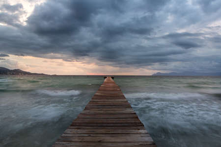 Dramatic Looking Morning at the Sea in Spain on Pier  Jetty - Majorca. Dark Clouds Before the Storm. Big Waves