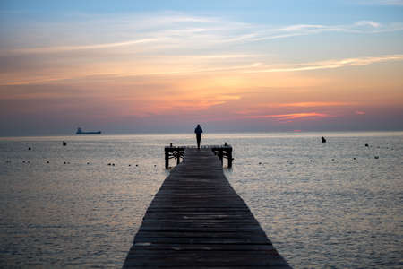 Person Watching the Sunrise on the Footbridge. Lonely Waiting for the Sun in the Middle of Pier  Jetty  Imagens