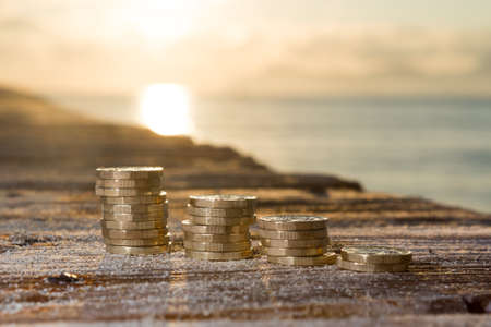 British Money, Pound Coins in Rising Stacks on Sandy Wood. New Pounds in a Warm Sunrise Light.