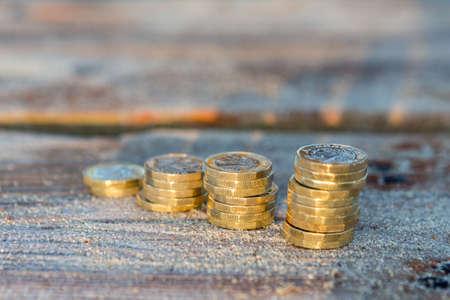 영국 돈, 샌디 우드에 상승 스택에 파운드 동전. 따뜻한 일출 빛의 새 파운드.