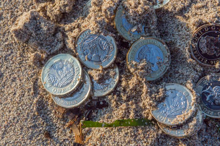 Pile of new Pound coins on the Beach Sand. New Pounds in a Warm Sunrise Light.
