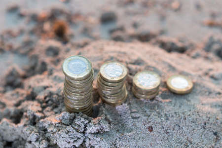 British Money, One Pounds Coins in Rising Stacks on Sand. New Pounds in a Warm Sunrise Light.