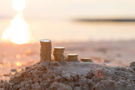 Coins in Rising Stacks on Sand Imagens