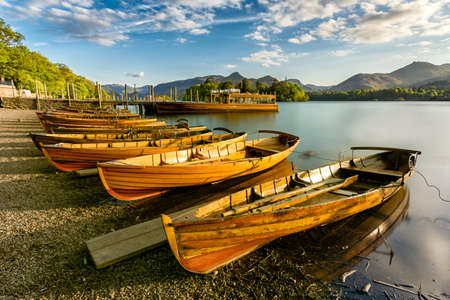 Wooden Rowing Boats lined up on shoreline being illuminated with golden light from the setting sun. Derwentwater, Lake District, UK.