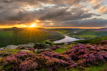 Evening sun bursting through dramatic clouds with epic view of Ladybower Reservoir in the Peak District. Stock Photo
