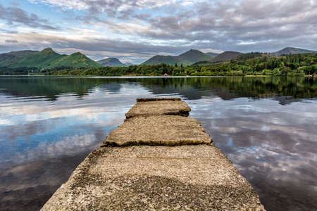 Calm summer morning at Derwentwater in the Lake District with stone jetty.