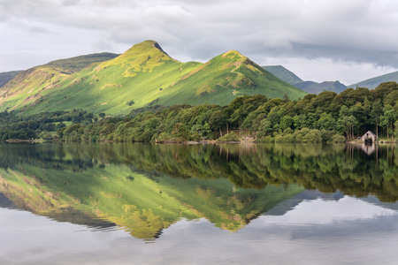 Green mountain peaks reflecting in calm lake with boathouse, Derwentwater, Keswick, Lake District, UK.