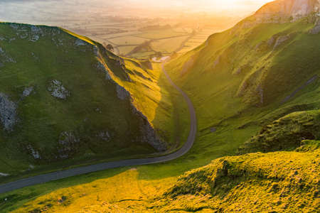 Long rural road leading through British countryside on a beautiful spring morning with dreamy light.