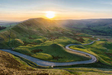Sunset at Mam Tor in the Peak District with long winding road leading through valley. Stock fotó