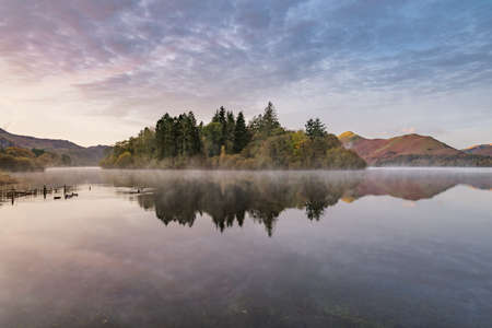 Beautiful calm reflections in a misty lake on a Autumn morning at Derwentwater in the English Lake District.