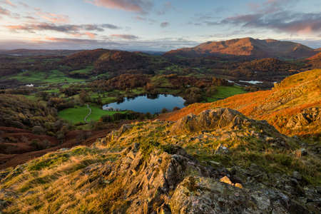 Loughrigg Tarn at sunrise on a Autumn morning with early light hitting the side of mountains. Taken in the English Lake District. 版權商用圖片