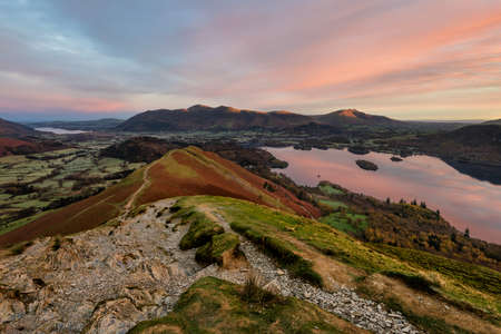 Beautiful subtle sunrise colours on a calm Autumn morning at the summit of Catbells overlooking Derwentwater in the English Lake District.