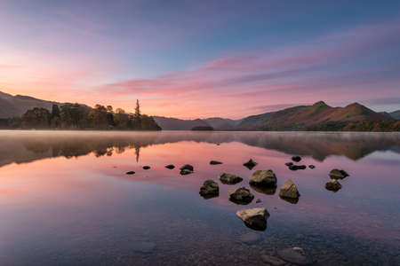 Beautiful pink and purple pre dawn sunrise sunrise with mirrored reflections in lake. Taken at Derwentwater in the English Lake District.