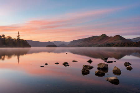 Beautiful pink sunrise reflected in a calm misty lake with rocks in foreground. Taken at Derwentwater in the English Lake District. Imagens