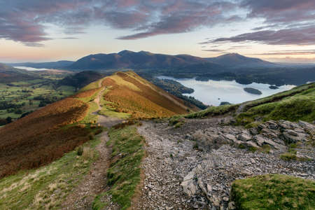 Rocky path on Catbells on an Autumn morning with sunlight hitting mountain and vibrant sunrise.