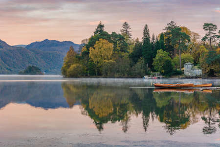 Wooden rowing boats with mountains and Autumn trees in background at Derwentwater in the English Lake District.