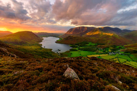 Moody dramatic clouds over high up view of Crummock Water at sunset. Lake District, UK.