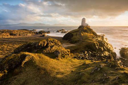 Llanddwyn Island Lighthouse with beautiful evening golden light after a rain storm.