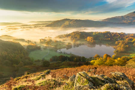 Beautiful Autumnal fog lingering over Windermere valley with Loughrigg Tarn in foreground.