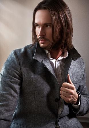 Bel homme avec longs cheveux bruns regarde par la fen�tre Banque d'images