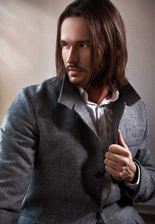 Handsome man with long brown hair looks through the window photo