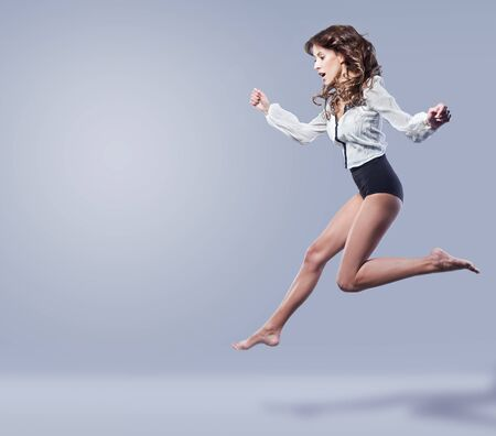 young beautiful brunette jumps on a blue background
