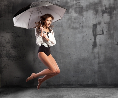 Studio Portrait Of Young Woman Jumping In Air with umbrella