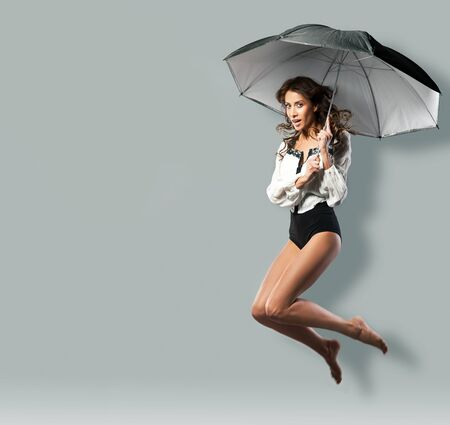 Studio Portrait Of Young Woman Jumping In Air with umbrella photo
