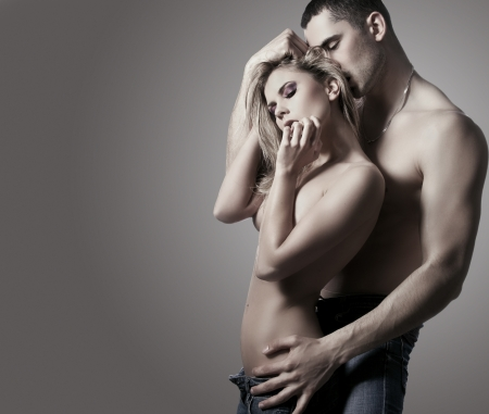 erotic: Portrait of romantic couple touching each other on a gray background