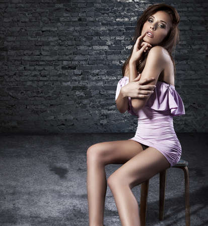 Stunning brunette sitting and posing on a chair in fashion dress photo