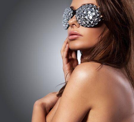 belle femme brune avec des lunettes de soleil sur fond gris