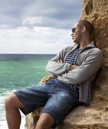 homme noir portant sur les rochers sur la plage en regardant vers l'eau �clair�e par le soleil, pensif Banque d'images