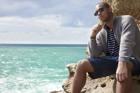 black man laying on the rocks on the beach looking toward the sunlit water pensively photo